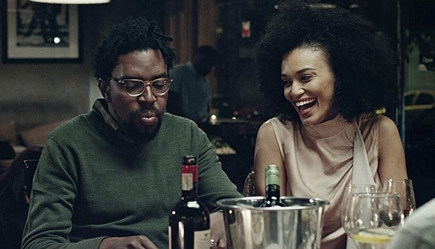 A man and woman enjoying dinner and drinks