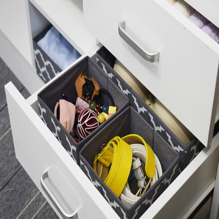An open drawer with two drawer dividers inside filled with rolled-up clothes and accessories