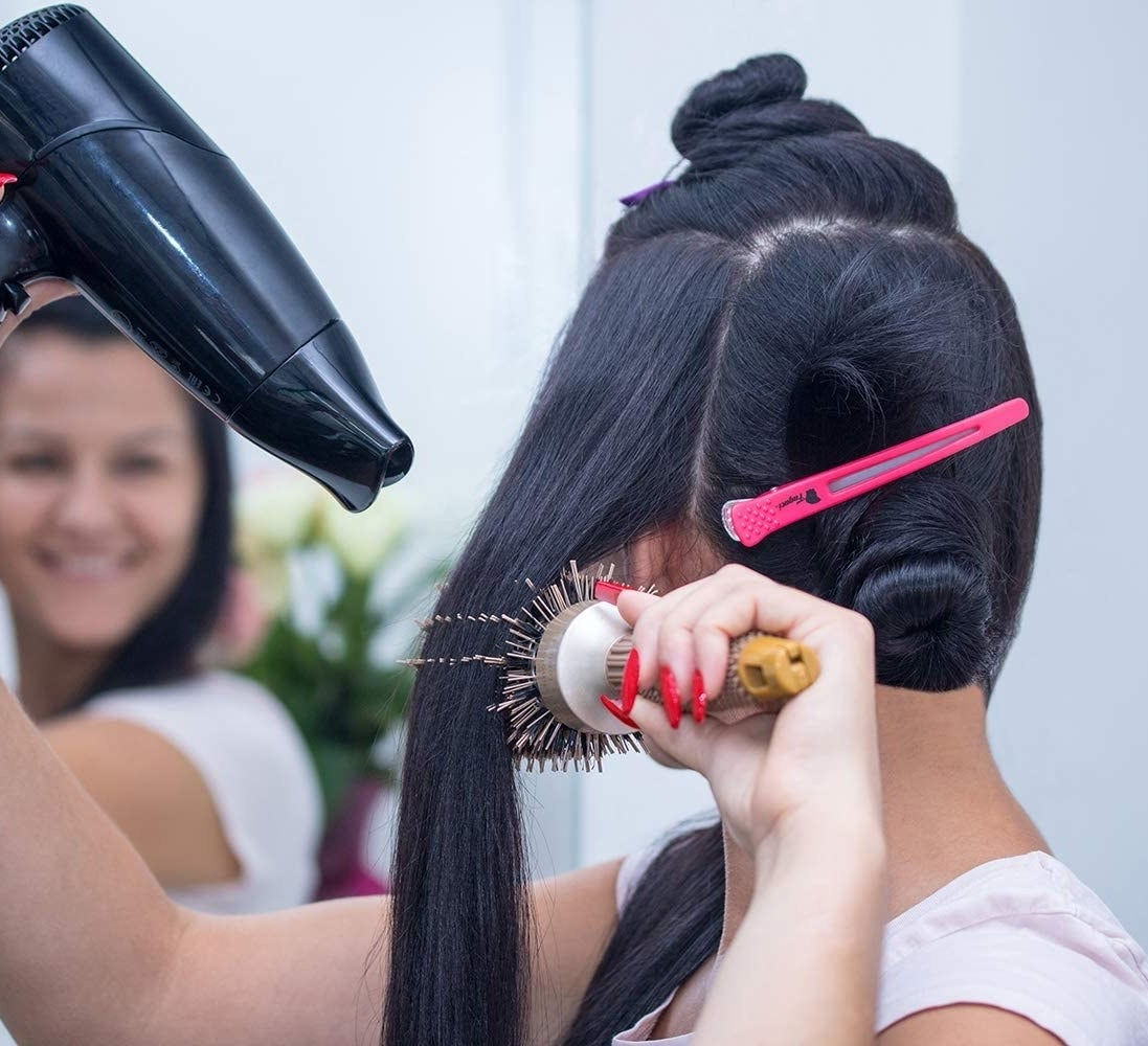A person blowdrying their hair with a clip holding an already styled piece in place