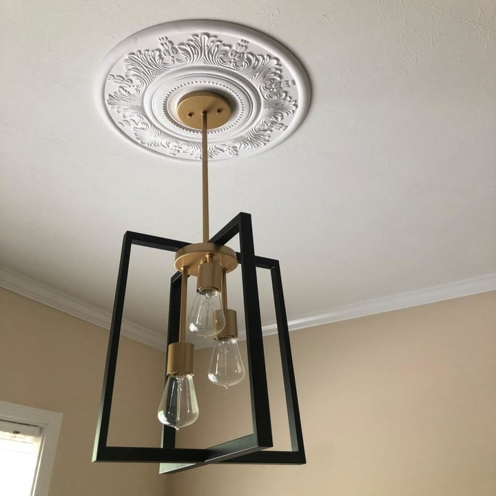 A reviewer's photo of the white medallion mounted beneath a pendant light