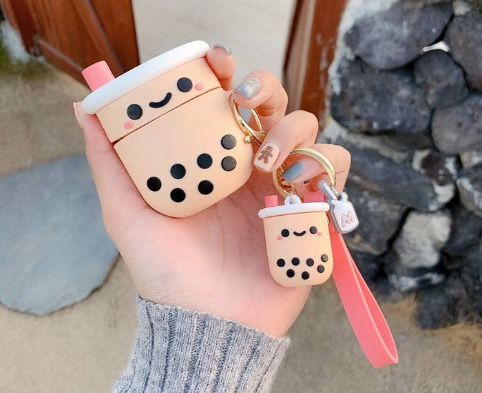 a person holding the boba airpods case and keychain