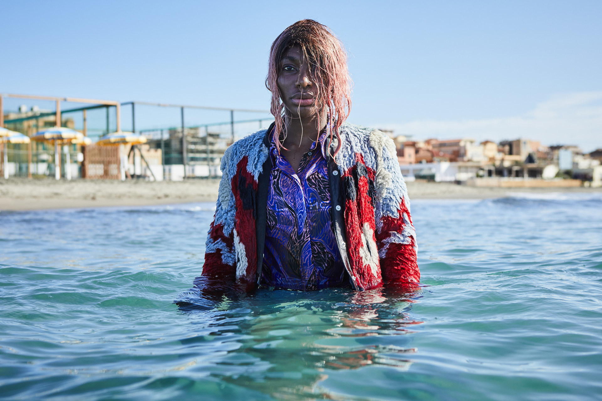 Michaela Coel standing fully clothed in the ocean in I May Destroy You