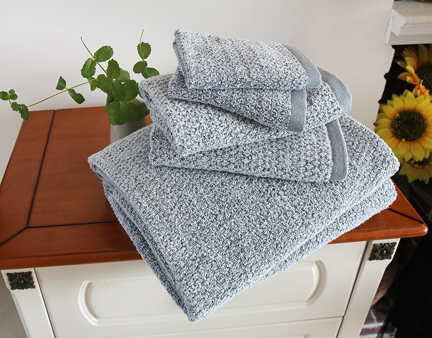a folded set of grey blue everplush diamond jacquard towels on a wooden cabinet