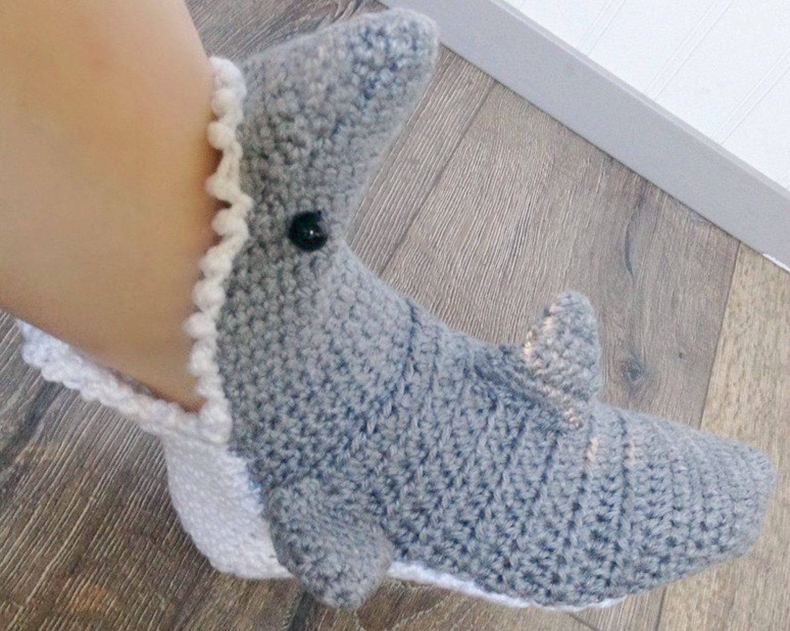 person wearing the crochet shark slipper on their foot