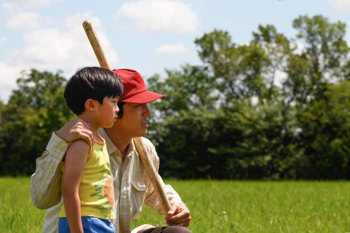 Steven Yeun crouched next to child actor Alan S. Kim in an open field in Minary