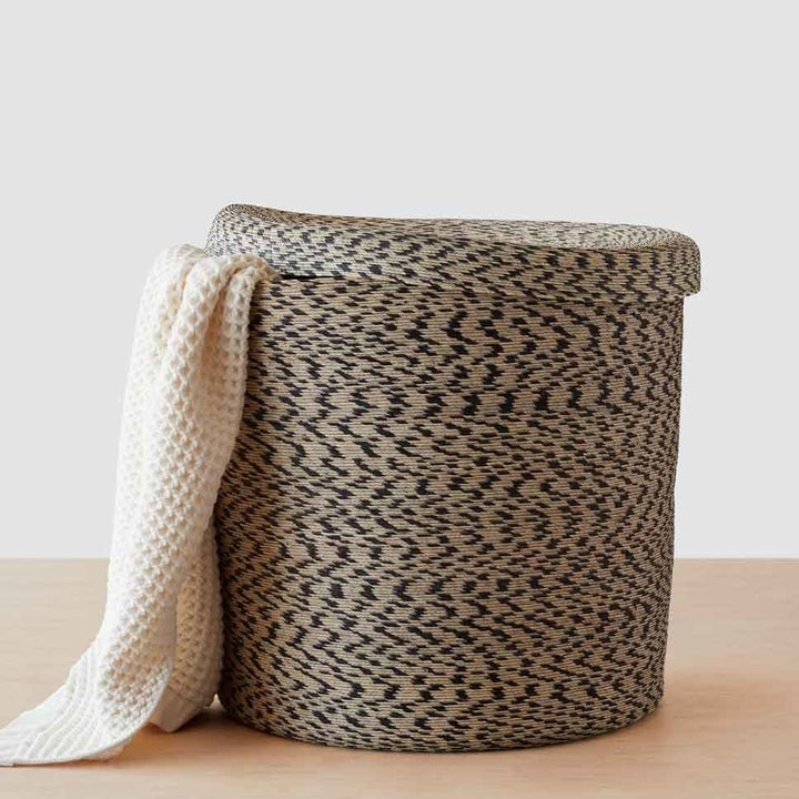 A woven basket with a lid and a throw blanket peeking out