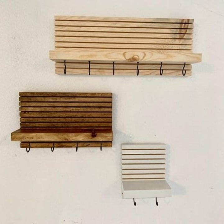 Three wall-mounted entryway organizers with multiple key hooks and a shelf in different sizes and colors