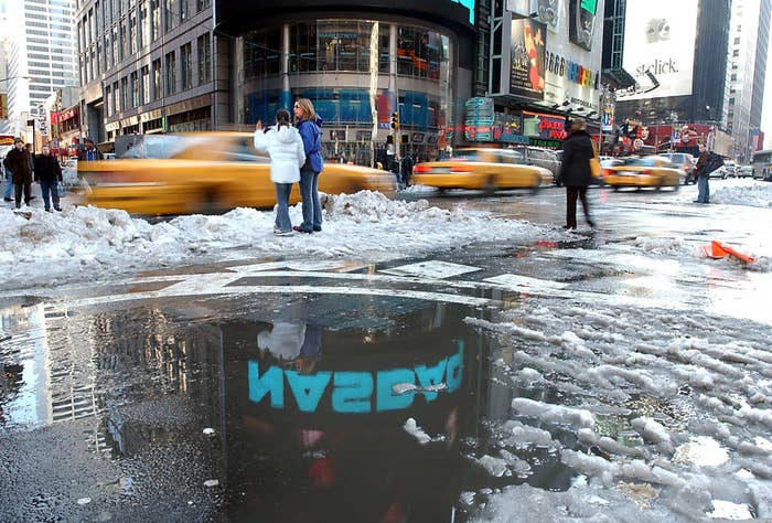 A pool of melted snow with a neon sign reflected in the dirty water as taxis drive by and pedestrians wait to cross the street
