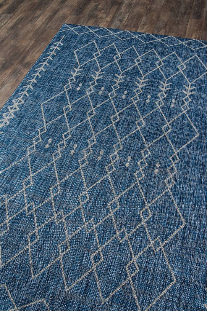 The rug in blue, which has a gray print of interlocking triangles in outline