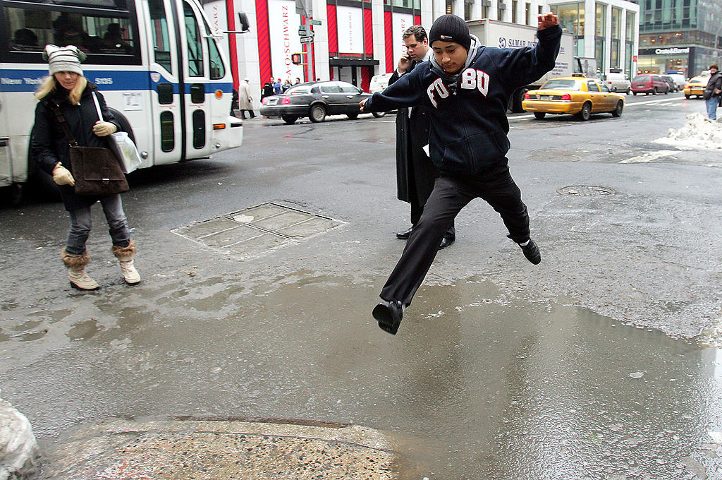 A man wearing a FUBU jacket commits and leaps across a slush pool