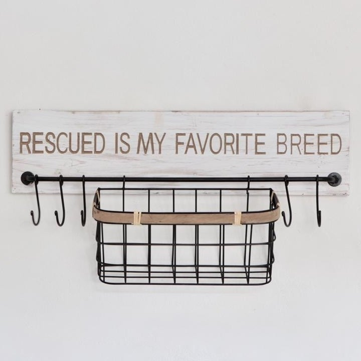 """A wall-mounted sign that says """"Rescued is my favorite breed"""" with an attached wire storage basket and five hooks"""