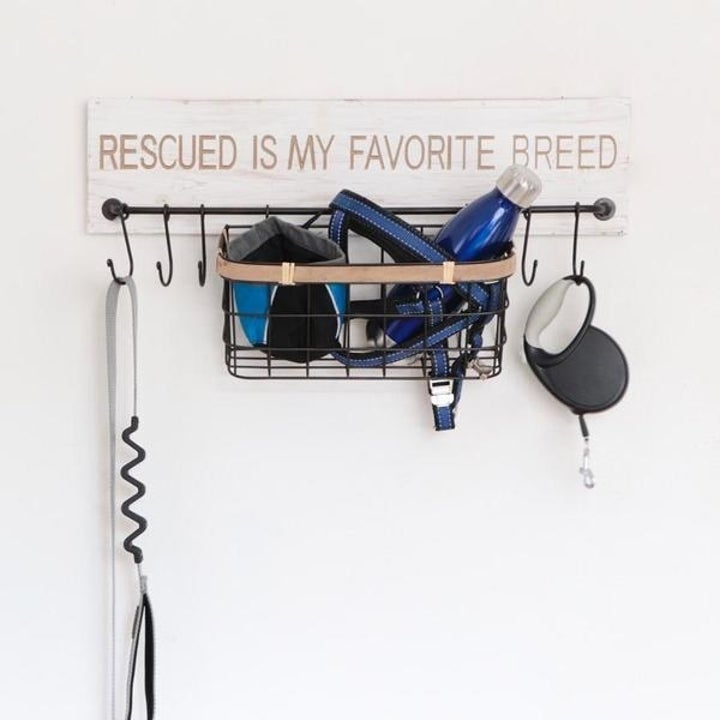"""A wall-mounted sign that says """"Rescued is my favorite breed"""" with an attached wire storage basket and hooks with leashes handing from them"""