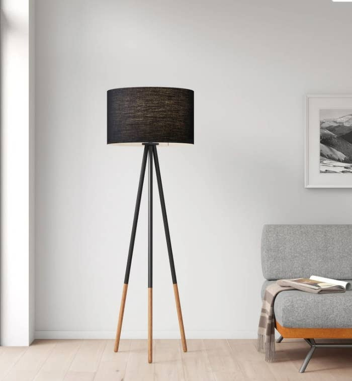 Black tripod floor lamp with black fabric shade and black/wooden legs