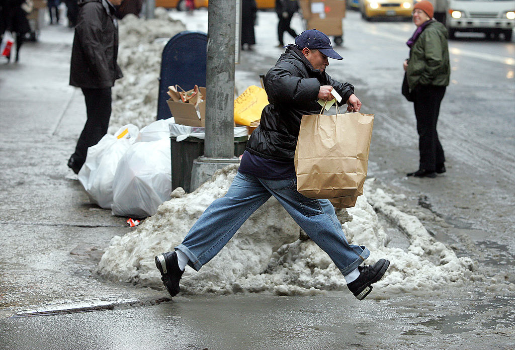 A man carrying a paper bag trues to jump across a large pool of filthy slush so he can cross the street