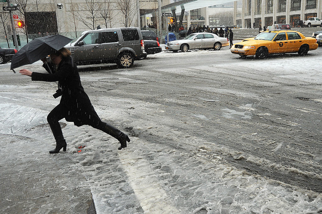 A person carrying an umbrella and walking in boots over a slushy street