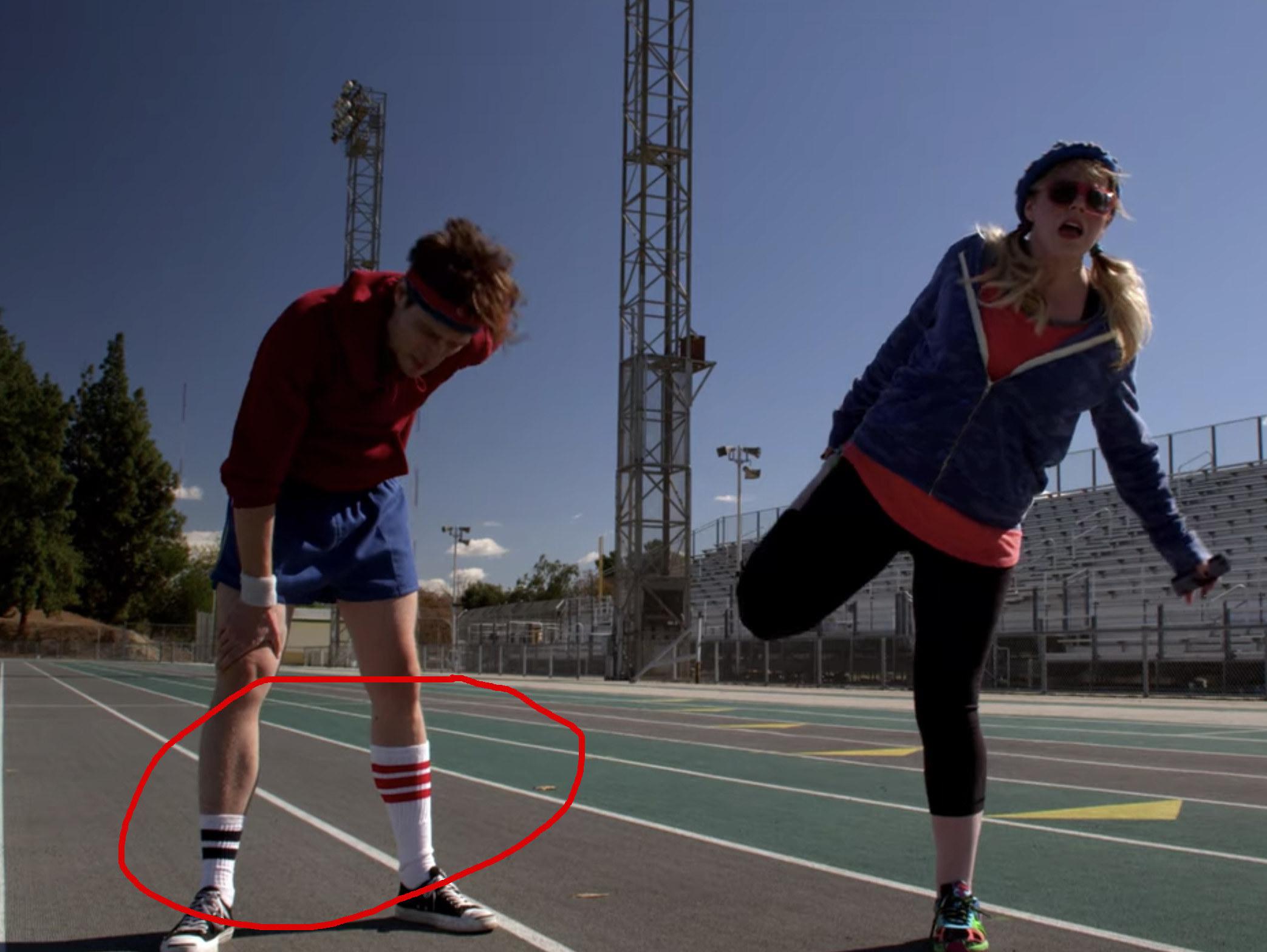 Dr. Reid wearing mismatching socks on a track field