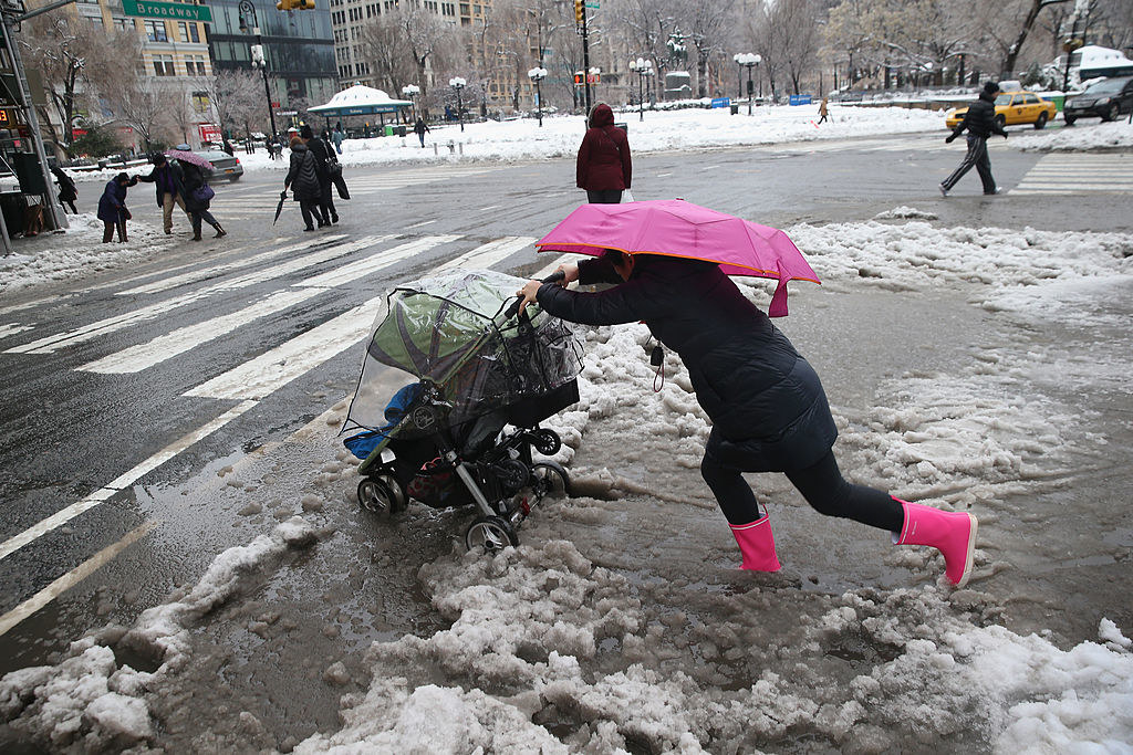 A person trying their best to push a child in a stroller through slush so they can go across a walkway