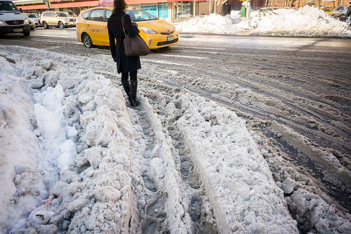 A person standing in plowed snow where a vehicle has driven through as they wait for traffic to stop
