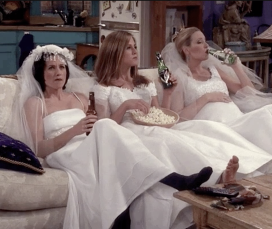 Monica, phoebe, and rachel in friends sitting on the couch watching TV in wedding dresses
