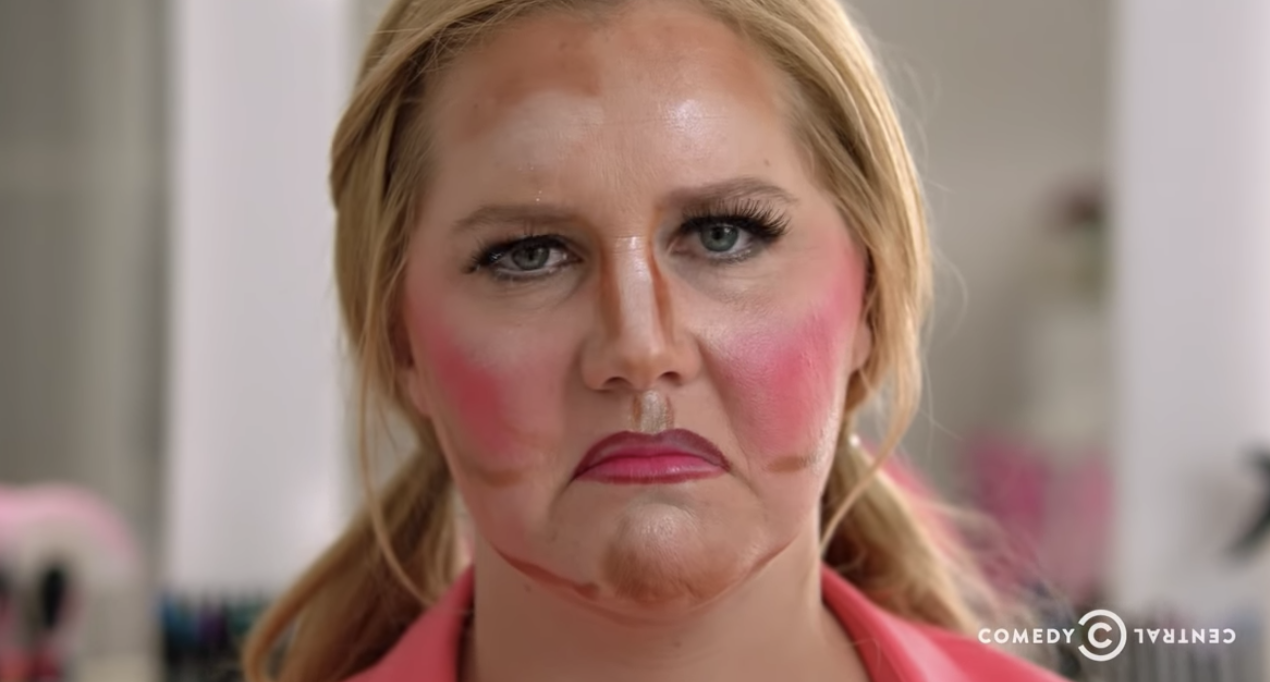 """Amu Schumer in the """"girl you don't need makeup video"""" with a face full of terrible makeup, looking sad"""