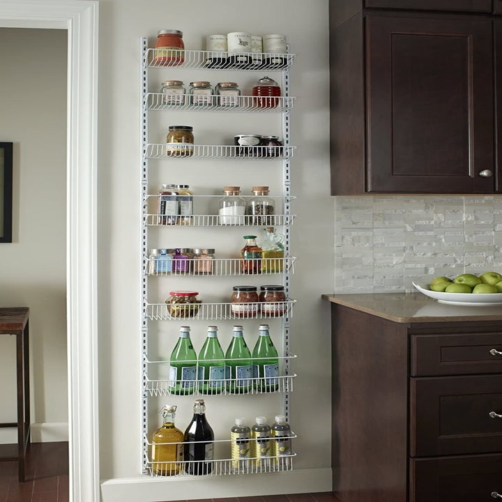 the white tiered rack mounted to the wall and filled with pantry items