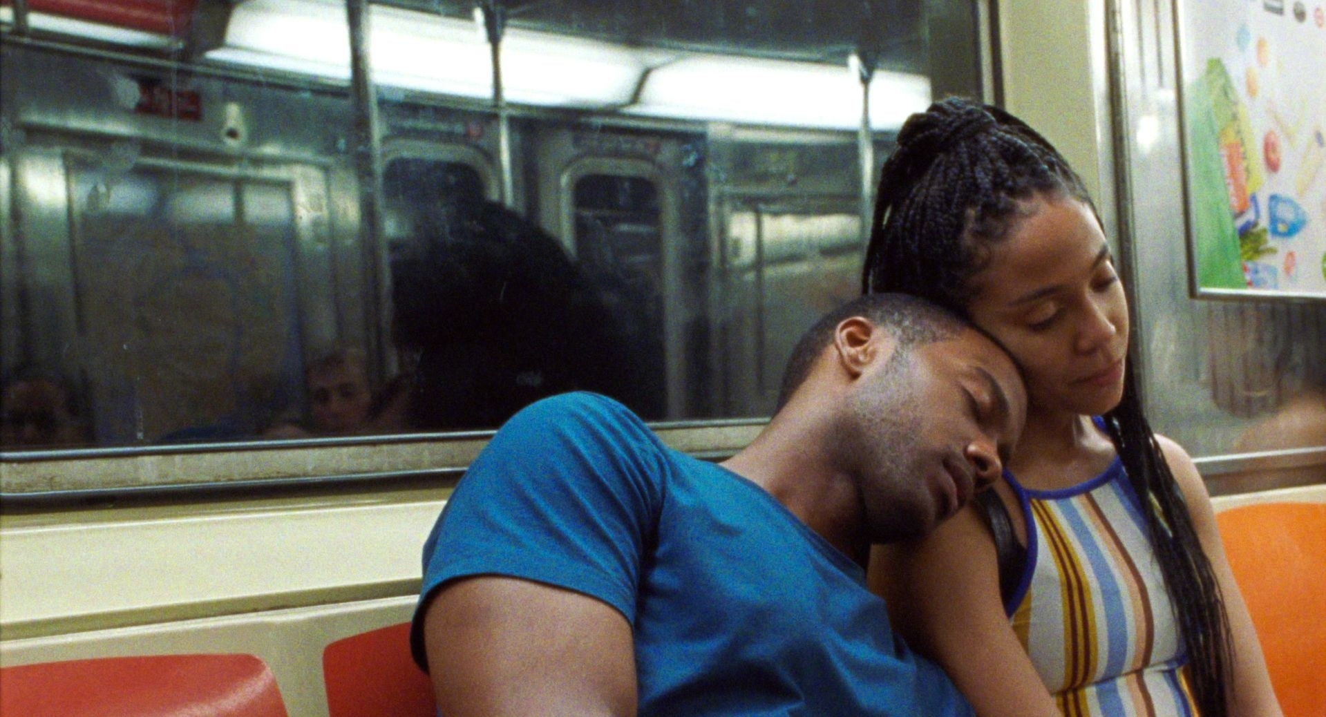 A man and woman lean on each other as they take the subway home