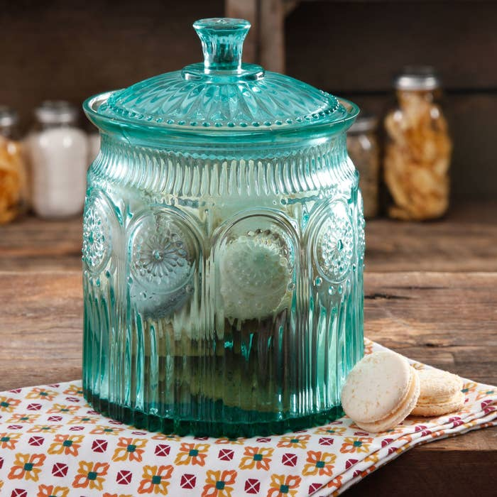 The cookie jar, which is a clear turquoise with pressed glass designs and a fully removable top
