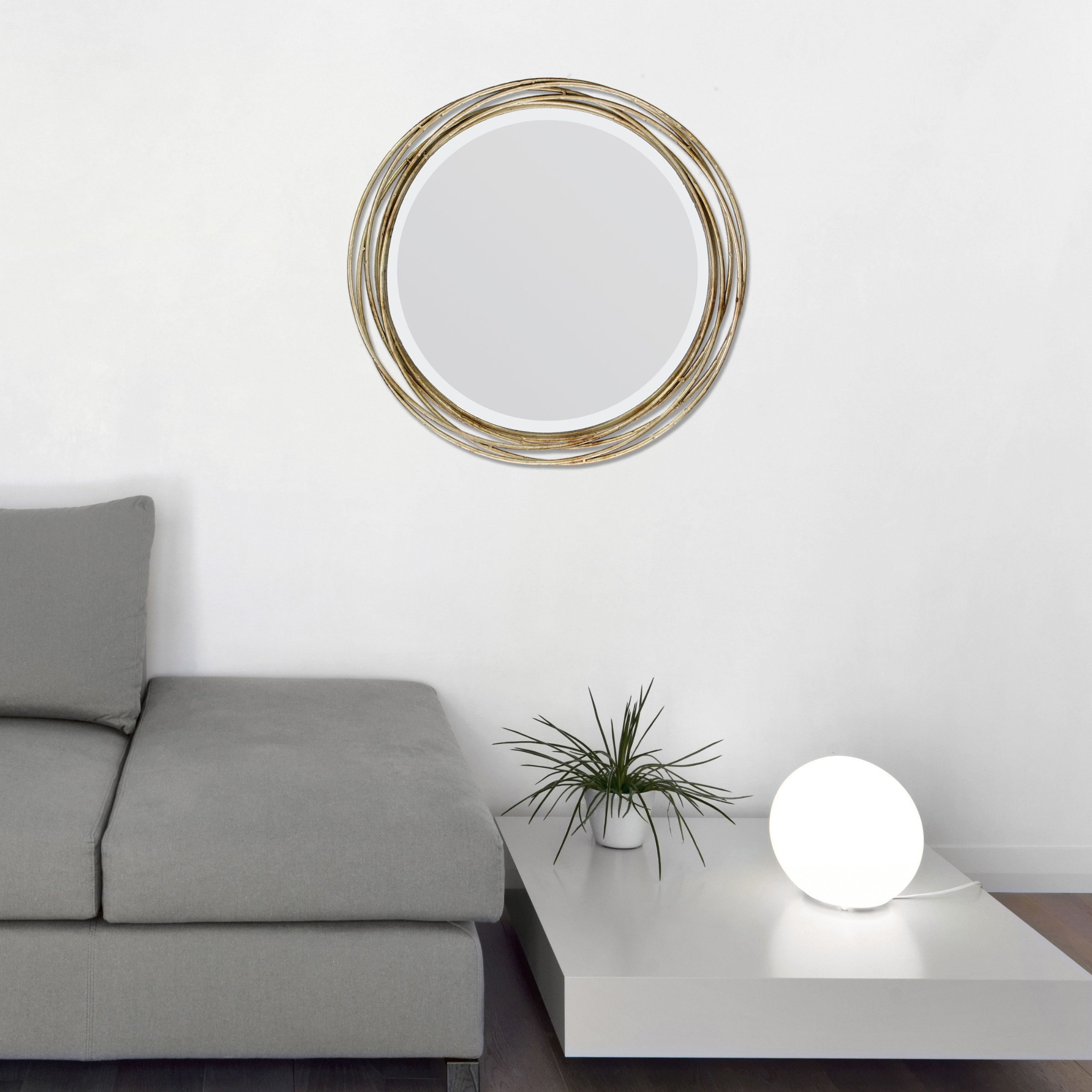 The mirror, which is round and surrounded by several loops of gold-toned wire
