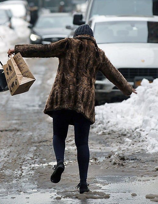A person with their arms raised for balance as they navigate through the snow and slush