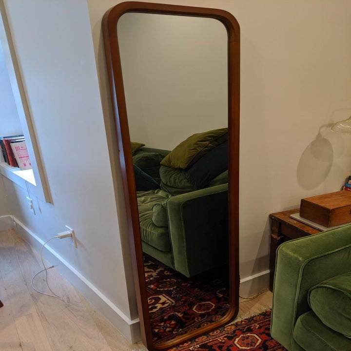 reviewer image of the tinytimes full length mirror leaning against a living room wall