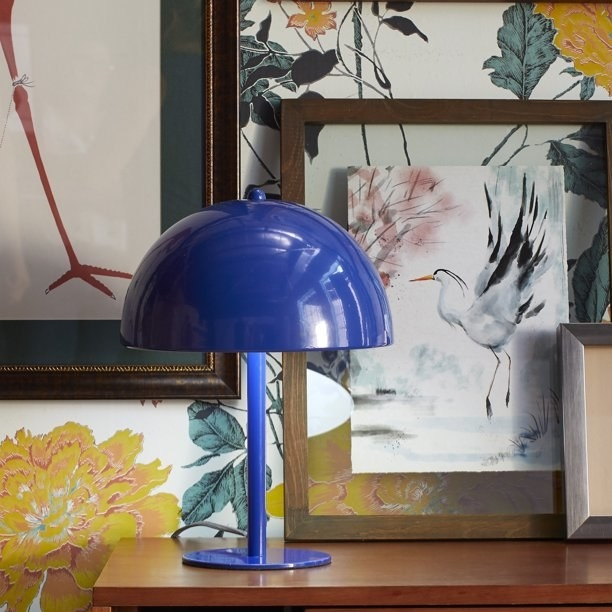 The lamp, which is royal blue and has a flat circular base, a narrow column, and a round, bowl-shaped metal shade