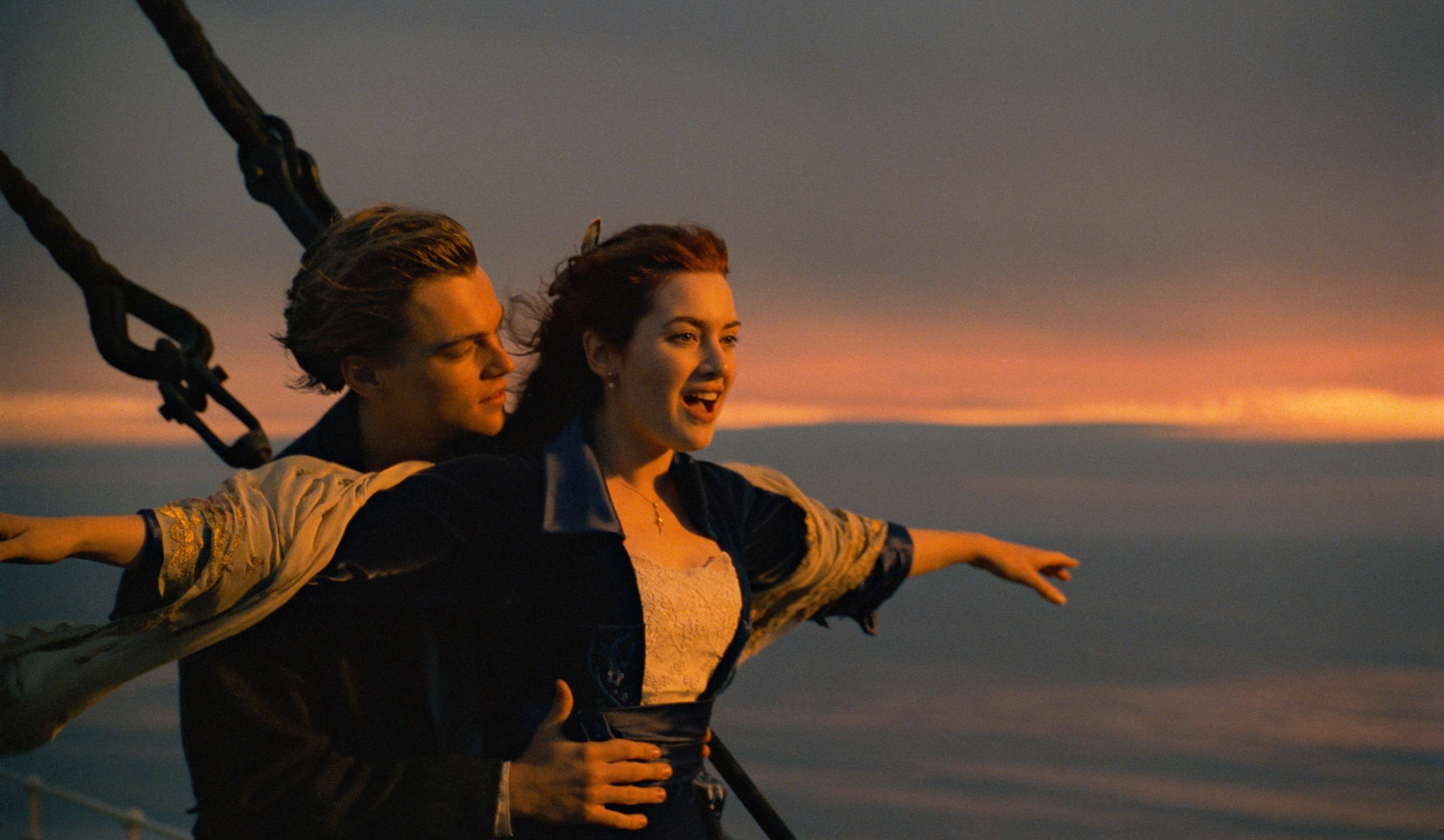 Leonardo DiCaprio holds Kate Winslet at the front of the Titanic with her arms outstretched in the film Titanic