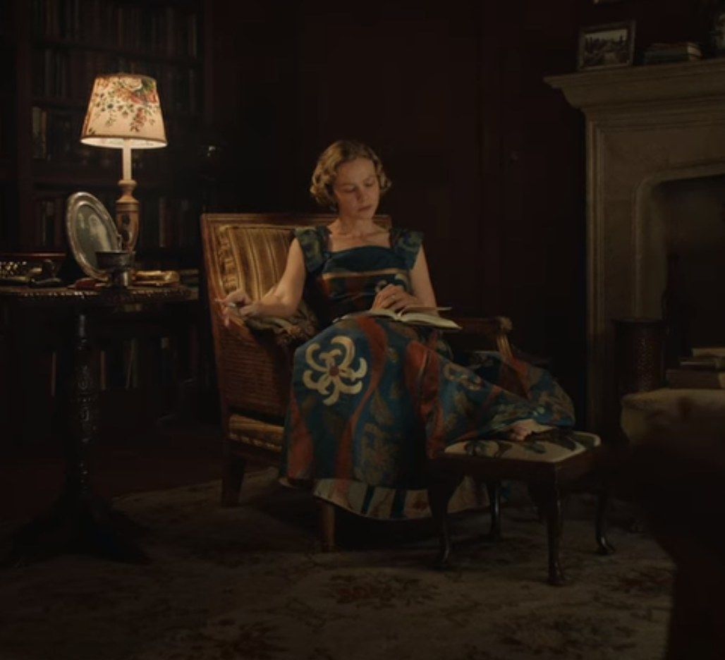 Still from The Dig: Mrs. Pretty in a colorful evening gown sitting in a library