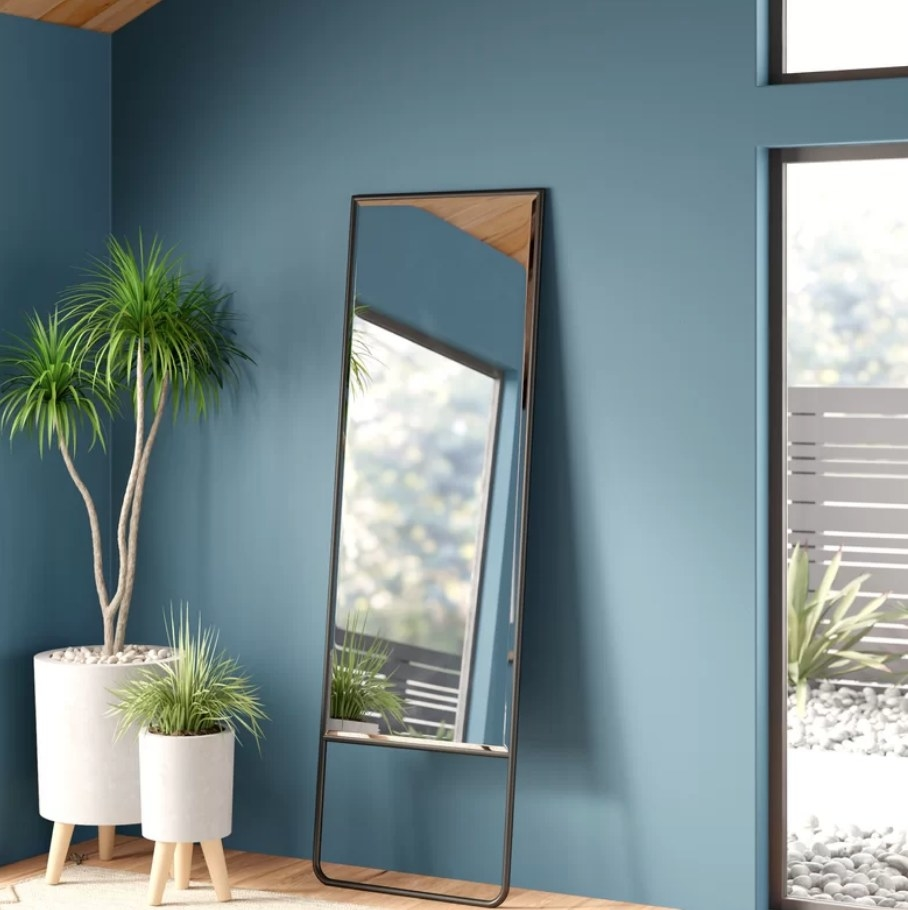 Full-length mirror with iron casted border leaning against a wall