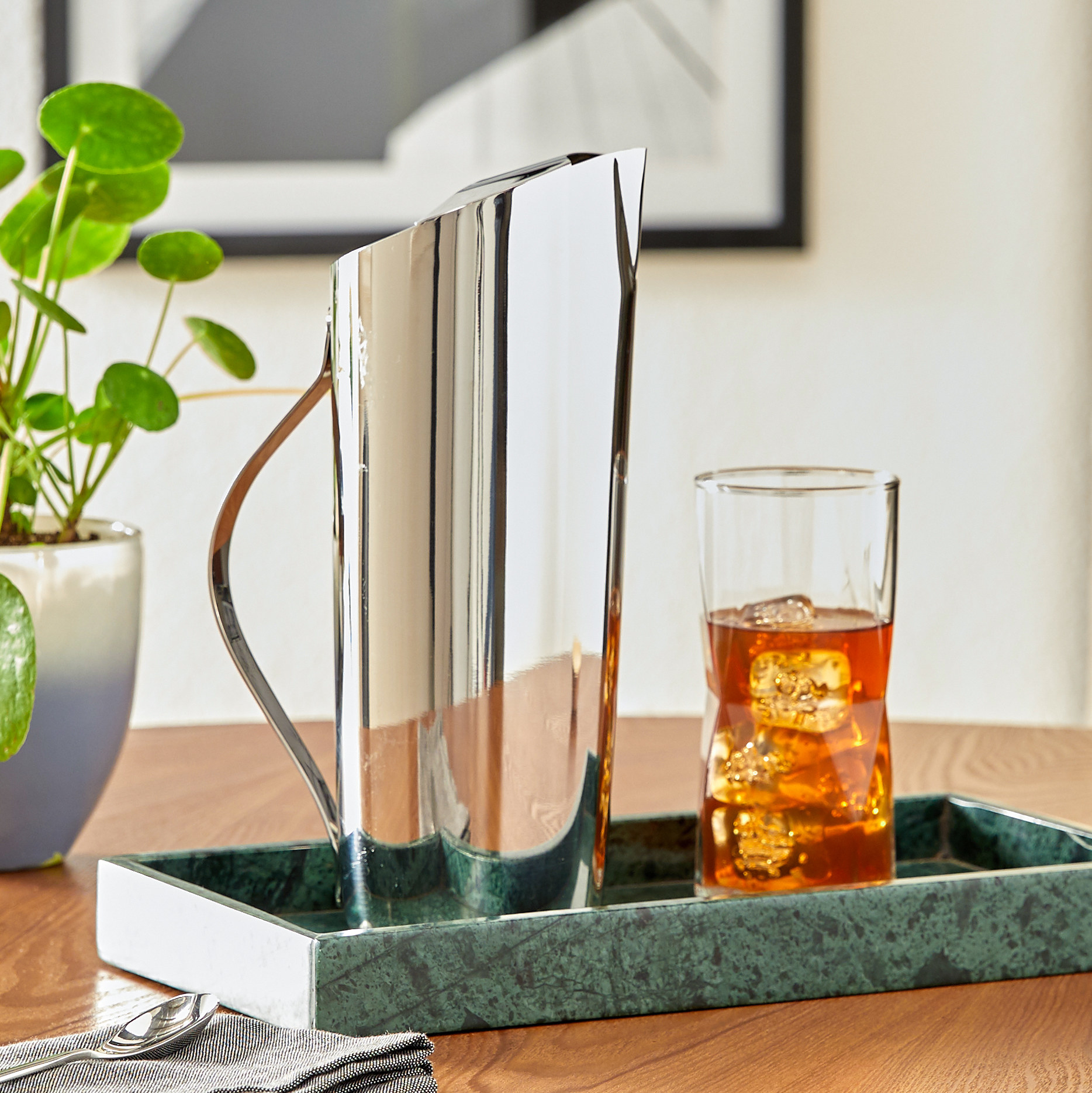 The pitcher, which is slim, has a handle, and an asymmetrical top that forms a spout