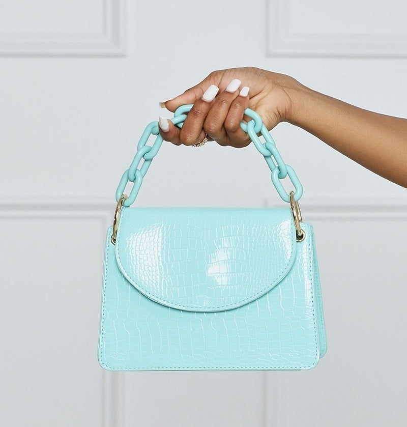 Hand holding the small aqua bag with top flap and chain link handle