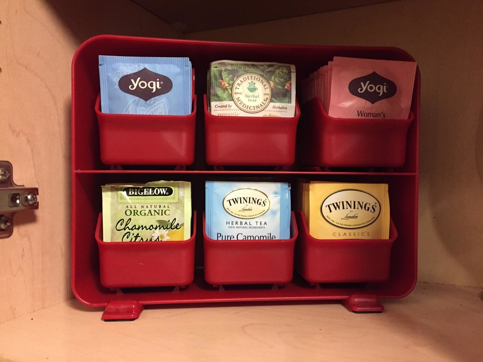 The tea bag holder in red with all six drawers filled with different indiivdually-wrapped tea bags