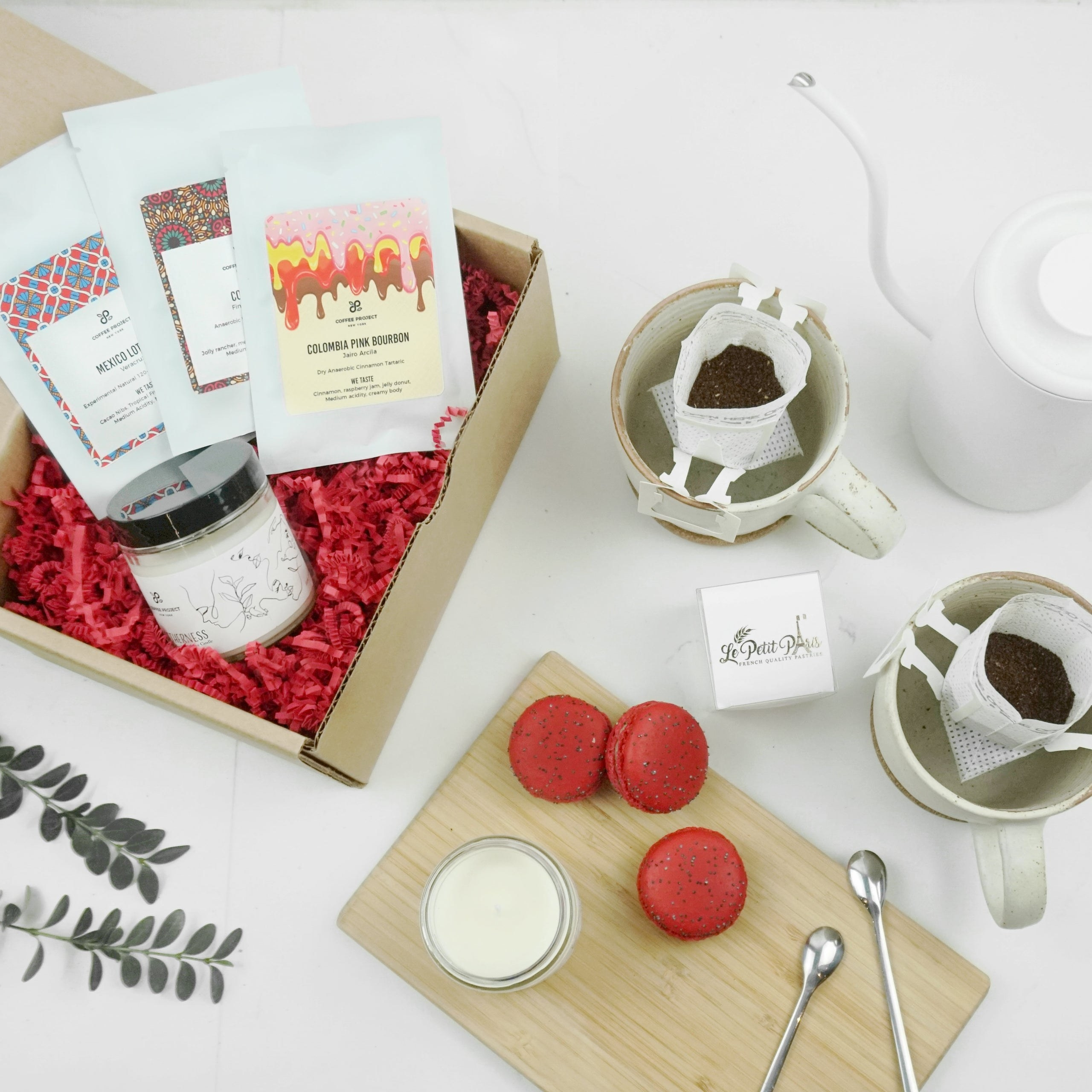 The gift set with coffee packets, a coffee-themed candle, and three red macarons