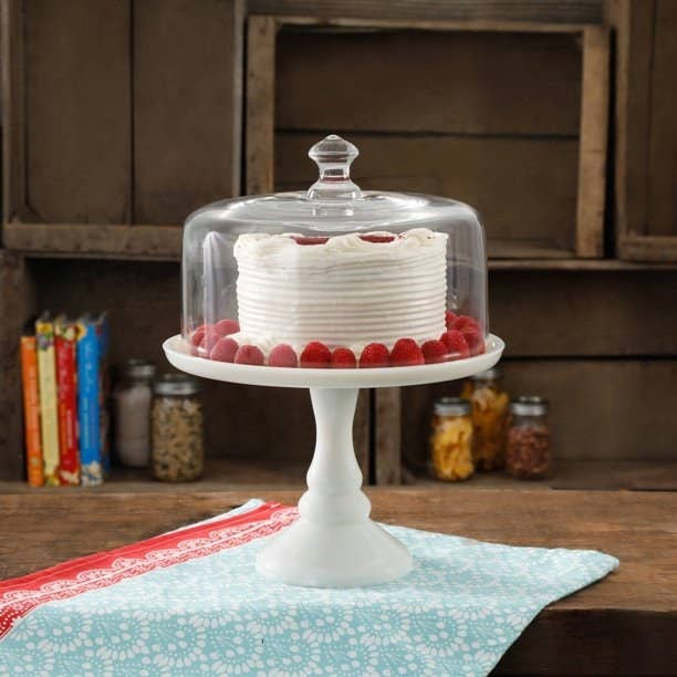 white cake stand with glass cover on a table, cake inside