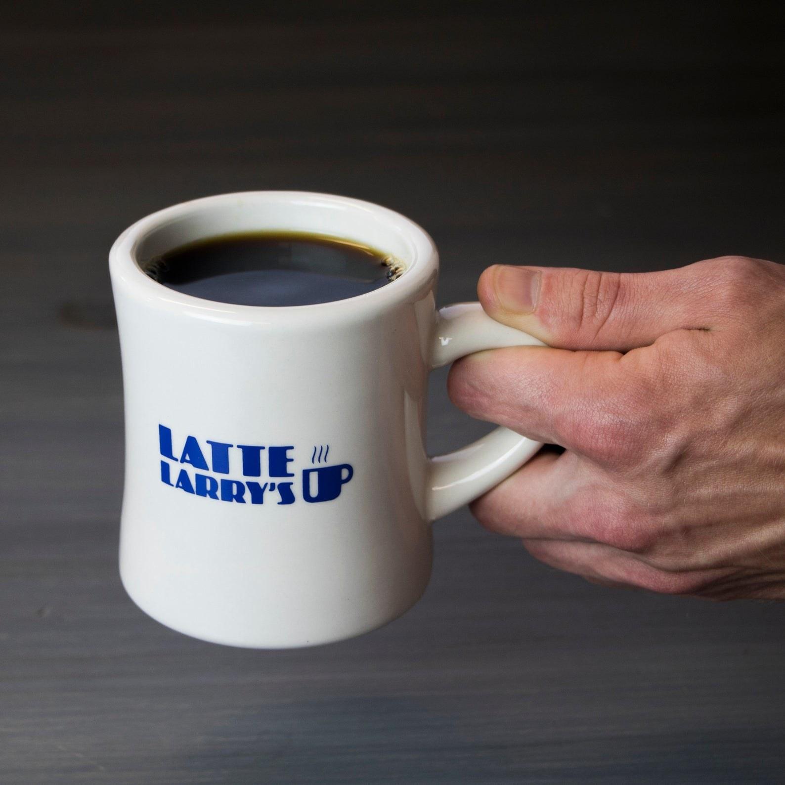 "Model holding the mug that reads ""LATTE LARRY'S"" with a little mug illustration"