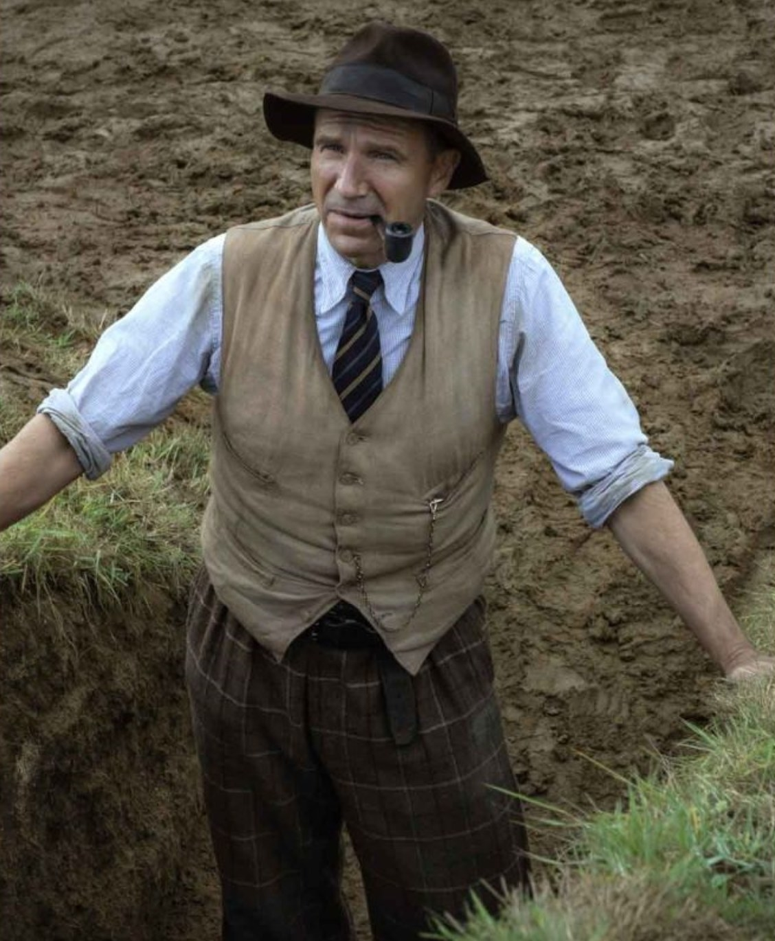 Still from The Dig: Basil Brown in vest, button-down, and trousers at the excavation site