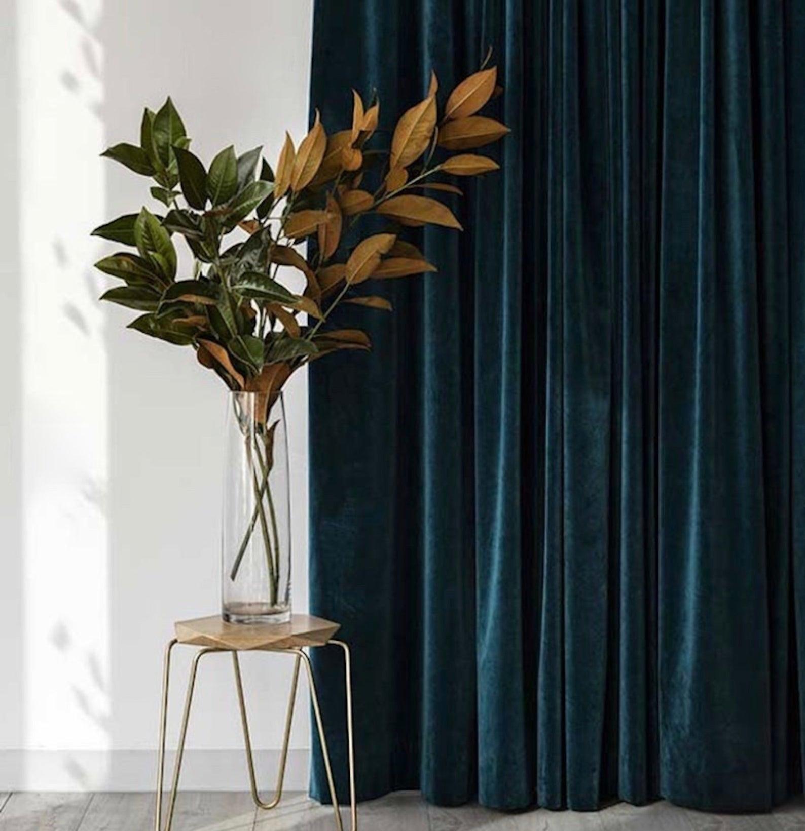 an indigo velvet curtain panel hanging from a window