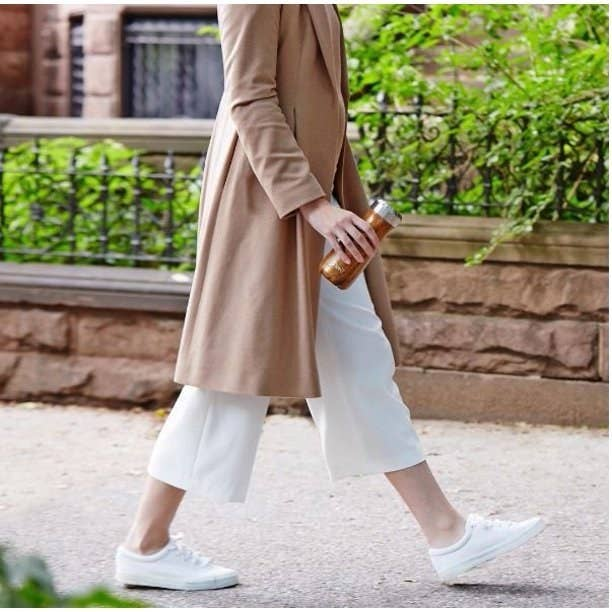 woman walking holding a teakwood S'well Traveler bottle