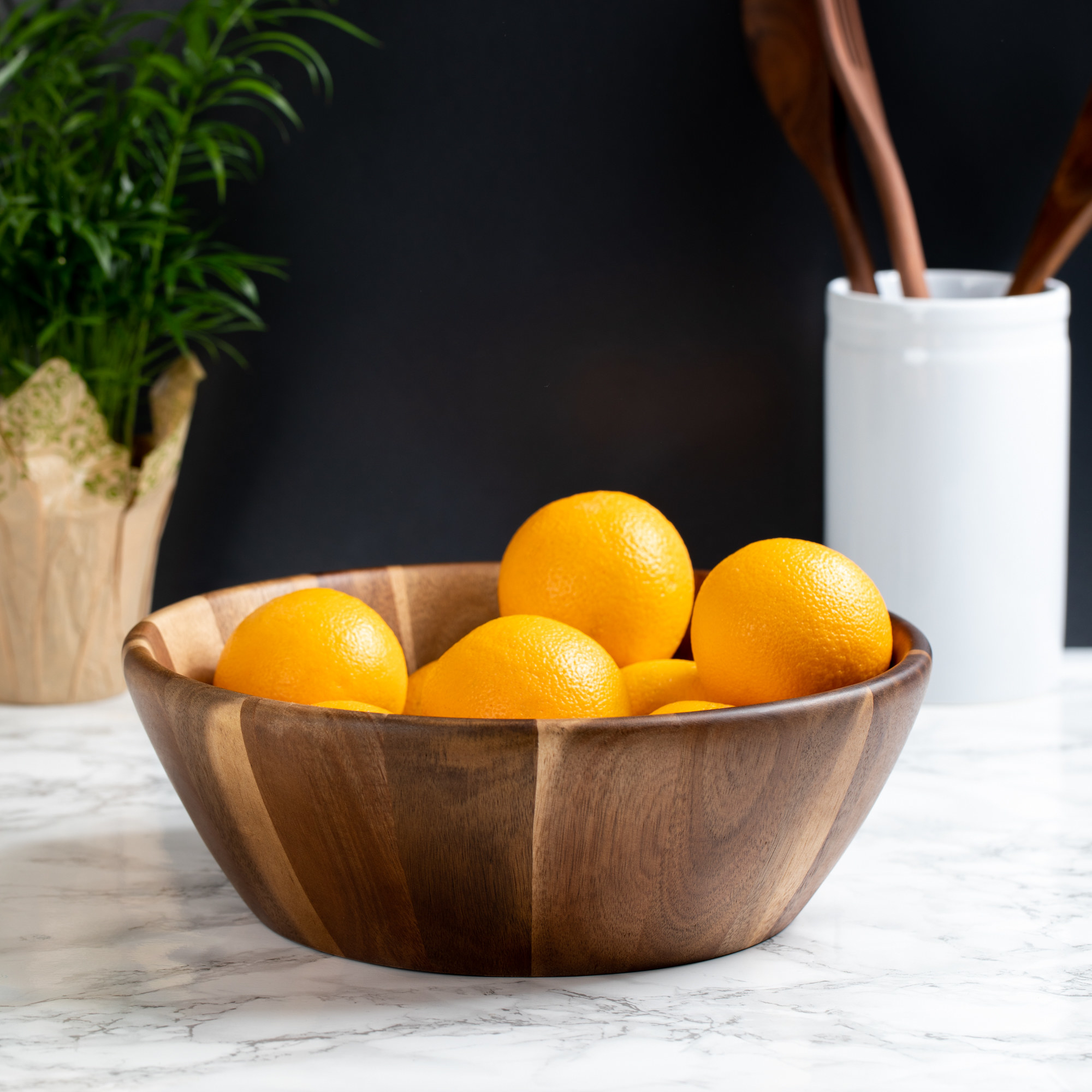wood bowl on a table with oranges inside