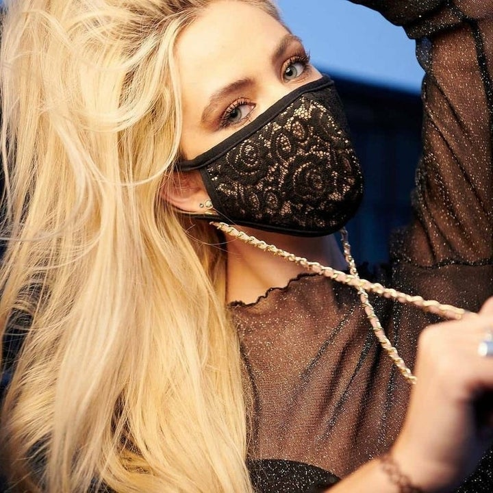 Model in a gold lanyard face mask chain attached to their face mask