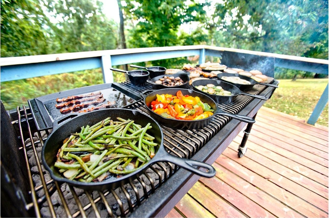 Cast iron skillets being used to cook outside