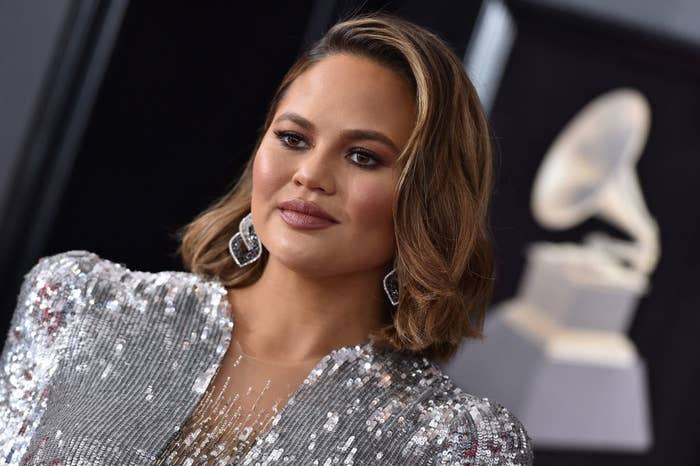 Chrissy on the Grammy's red carpet wearing a sequined dress, drop earrings, and her hair down