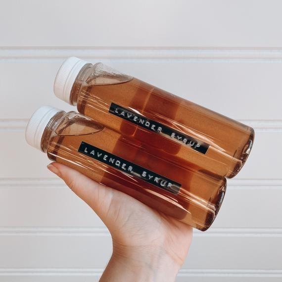 Bottles of lavender simple syrup in hands