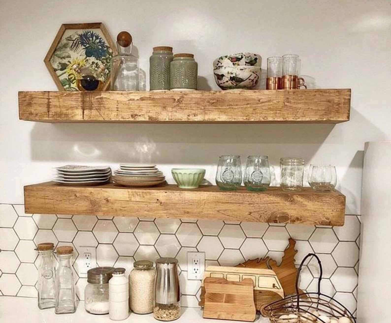 the wooden shelves hanging in a kitchen and holding things like dishes, cups, and decorative pieces