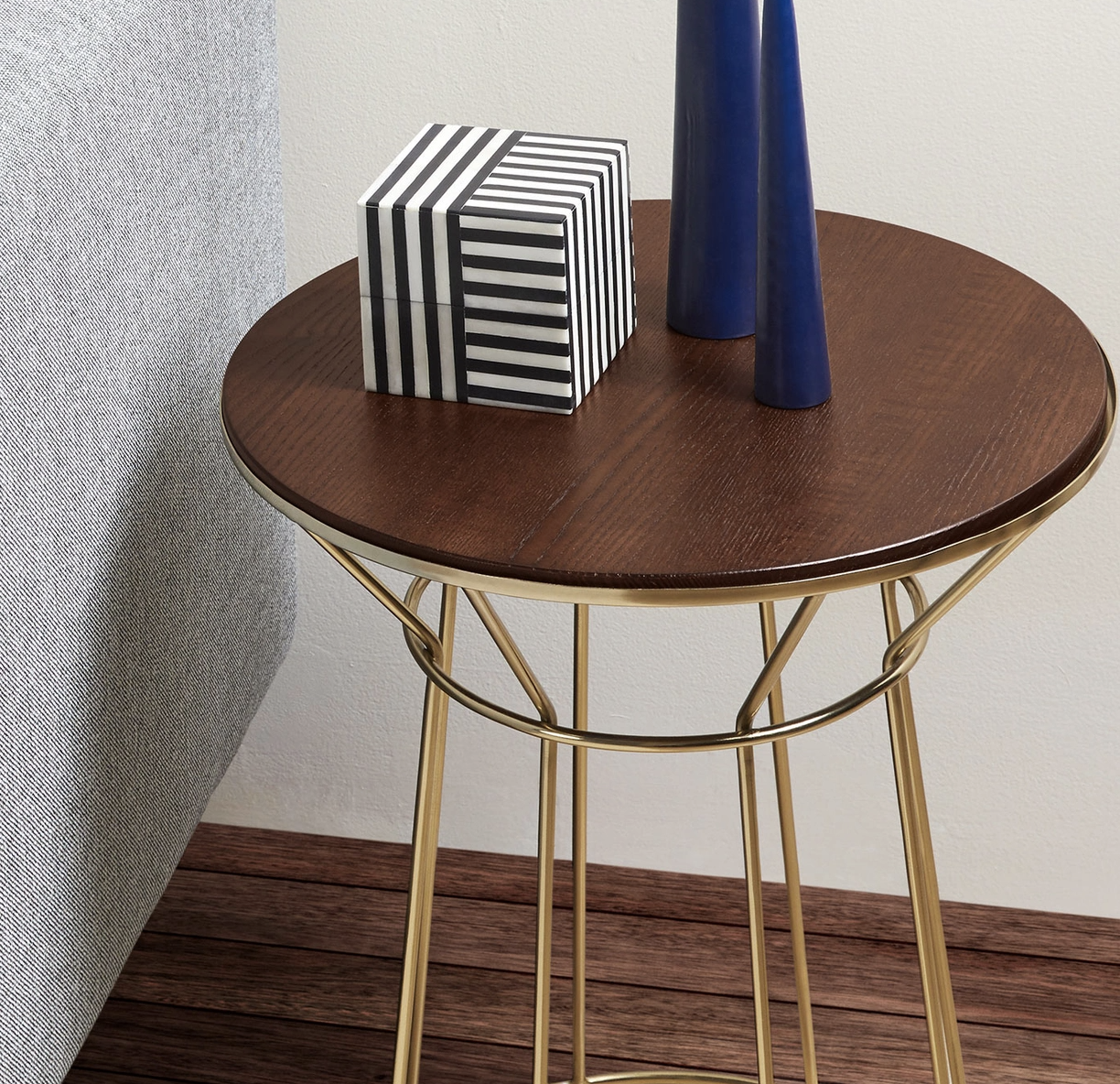 a rounded side table with a wooden top and gold legs